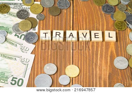 Word TRAVEL on wooden cube with money frame at wood background.