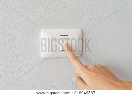 Close up of woman finger turning on light switch with white background copy space.