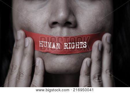 Young woman was wrapping her mount by adhesive tape Concept freedom of speech censorship freedom of press. International Human Right day.