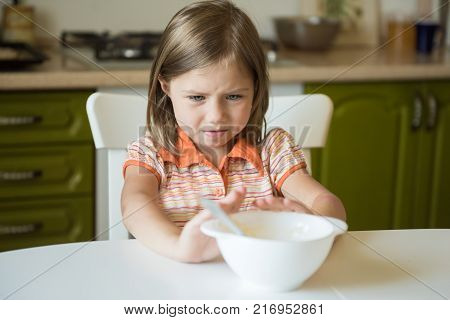 Cute little girl refuses to eat, pushes the plate