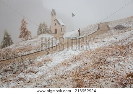 Chapel with first snow in Passo Gardena, Dolomiti Mountains, Alta Badia, Italy