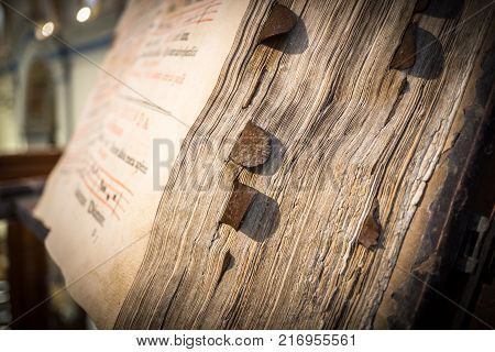 detail of the pages and bookmark of a church choir books on a wooden lectern. Very old deteriorated books 16th century, vintage