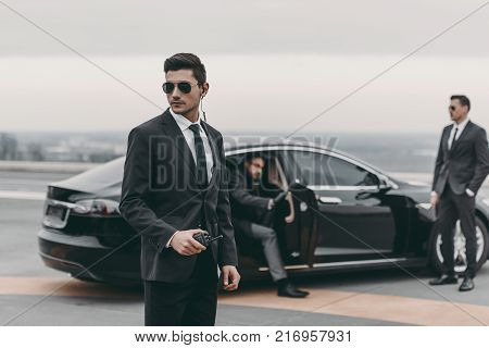 bodyguards going with businessman and reviewing territory near car