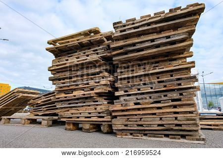a large stack of wooden construction pallets outside