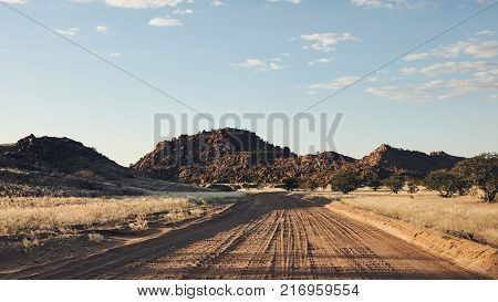 Large dirt road in Namibia wandering around Africa matte style.