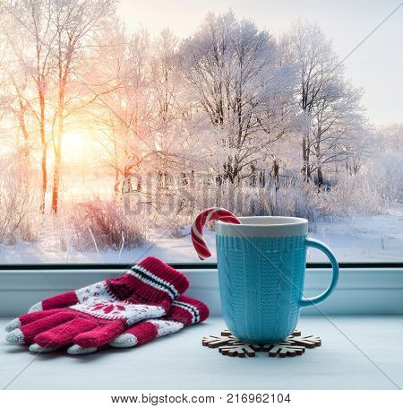 Winter background. Cup with candy cane on windowsill and winter trees outdoors. Winter still life with winter Christmas mood. Cozy winter composition. Festive winter still life, winter background
