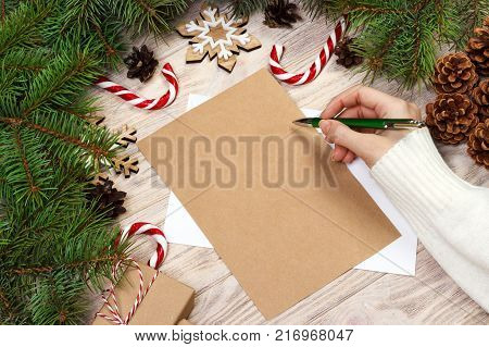 Famale hand writing a Christmas letter on wooden background.