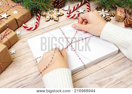 Many envelopes tied with rope. Close-up top view of famale hands with envelope. Pine cones and christmas decoration on old wooden table desk.