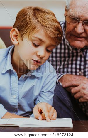 Portrait of diligent little schoolboy sitting at table and reading book with grandparents touching pages. Senior man and woman wearing glasses looking at grandson and smiling