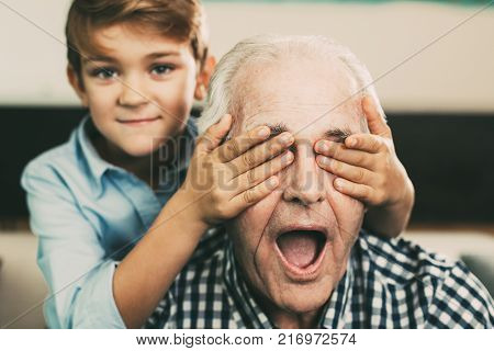 Portrait of little Caucasian boy making surprise covering eyes of senior grandfather at home
