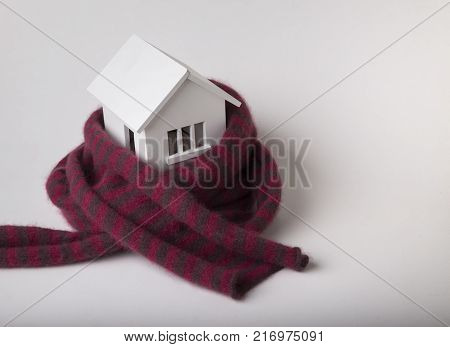 house in winter - heating system concept and cold snowy weather with model of a house wearing a knitted cap.