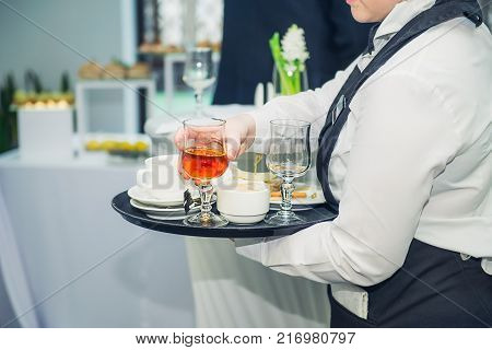The waiter removes dirty dishes from the tables after guests of the event. Catering Service at business meeting, party, weddings. Food Celebration Party Concept. Selective focus, space for text.