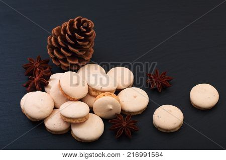 Holiday food concept French Star anise macarons decor by pine corn and star anise on black slate stone plate