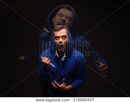 A guy addict in a blue sweatshirt with a syringe in his hand euphoric from the dose rolled his eyes against a black background