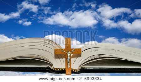 Open book with a cross against a blue sky with white clouds