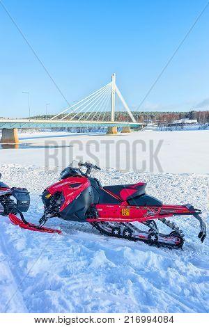 Rovaniemi Finland - March 4 2017: Red snowmobile in frozen lake at Candle bridge in winter Rovaniemi of Lapland Finland