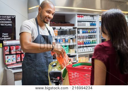 Smiling salesman putting vegetables in bag for customer after billing. Cashier black man at grocery store helping customer pack purchased products. Happy young man working in grocery shop.