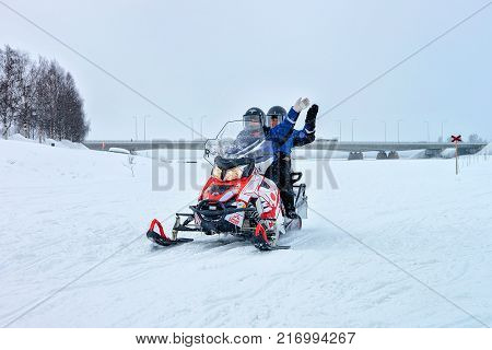 Rovaniemi Finland - March 2 2017: People waving hands while riding a snowmobile on the frozen lake in winter Rovaniemi Lapland Finland