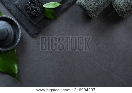 Top view of two gray rolled towels with hot stones pile with copy space. High angle view of male beauty treatment set with leaf and black salt. Luxury and elegant spa setting on black background.