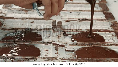 liquid chocolate in chocolate fabric, making chocolate bars. pouring chocolate