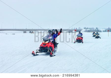 Rovaniemi Finland - March 2 2017: People waving hands and riding a snowmobile in the frozen lake in winter Rovaniemi Lapland Finland