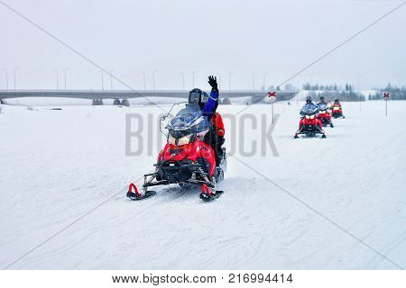 Rovaniemi Finland - March 2 2017: People riding snowmobiles and waving hands on the frozen lake in winter Rovaniemi of Lapland Finland