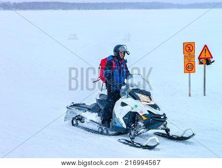 Rovaniemi Finland - March 2 2017: Man riding a snowmobile on the frozen lake in winter Rovaniemi Lapland Finland