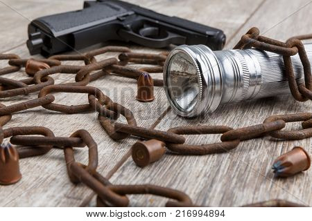A rusty chain, bullets, a gun and a silver flashlight lie on a wooden background