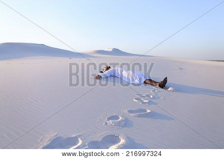 Successful Muslim tourist guy lies on on soft white sand and spreads hands to sides, smiles broadly,  laughs and smiles in vast desert on clear warm day. Swarthy, handsome Muslim with short dark hair dressed in kandura, long, spacious dress made of white