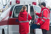 happy male and female paramedics reading documents in front of ambulance poster