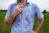 Man with hyperhidrosis sweating very badly under armpit in blue shirt because of hot weather. Travelling in asia thailand with backpacker poster