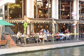 Blurred image of riverside restaurant in downtown San Antonio Texas USA. Riverfront popular dining places with colorful Christmas decoration along. People walking. poster