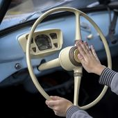 Close-up of hands of boy at the steering wheelof the retro car his great-great-grandfather, with interest testing beeping, sound signal poster
