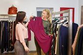 sales consultant helping chooses dress for the customer in the store. Shopping with stylist. Beautiful female shop assistant consulting young woman in the fashion boutique poster