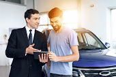 A man buys a new car in a light large car showroom. He is assisted by a dealer at the car dealership. There are many modern cars. poster