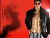 Fashion portrait of edgy male model wearing eye makeup in fur against red background poster