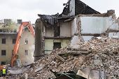 Half collapsed brick house covered in dust and debris with a crasher machine. poster