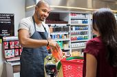 Smiling salesman putting vegetables in bag for customer after billing. Cashier black man at grocery store helping customer pack purchased products. Happy young man working in grocery shop. poster