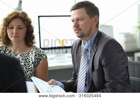 Portrait Of Businesspeople Sitting In Conference Room And Discussing Important Business Project With