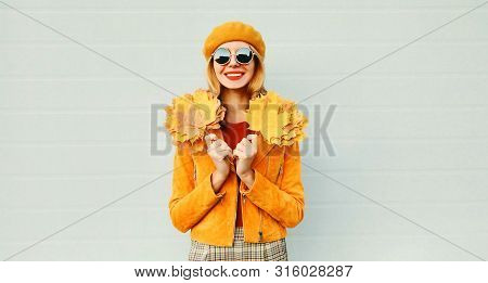 Autumn Portrait Happy Smiling Woman With Yellow Maple Leaves On City Street Over Gray Wall Backgroun