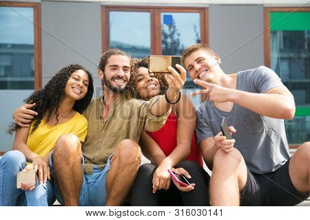 Happy Mix Raced Friends Taking Selfie Outdoors. Joyful Group Of Young People Posing For Phone Camera