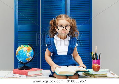 Smart Toddler Kid. Back To School And Happy Time! Cute Industrious Child In Glasses Is Sitting At A