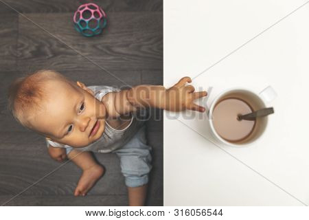 child burn and scald injury concept - little boy reaching for hot drink mug on the table poster