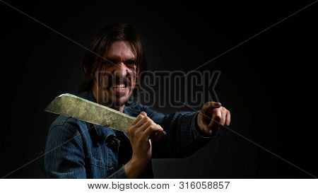 A Man Holds A Machete On His Shoulder And Points The Finger Of His Other Hand Forward. The Guy Is Vi
