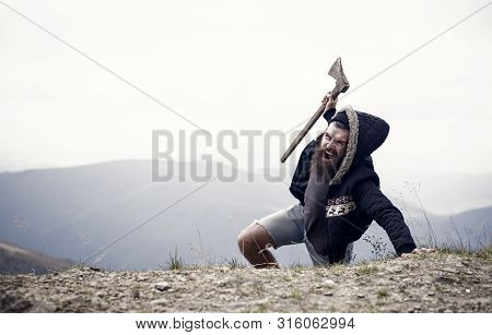 Man With Beard On Shouting Face Conquers Top Of Mountain With Axe, Sky Background. Survive In Wild N