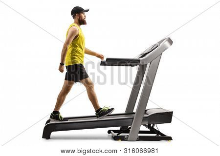 Full length profile shot of a bearded guy in sportswear walking on a treadmill with an incline isolated on white background