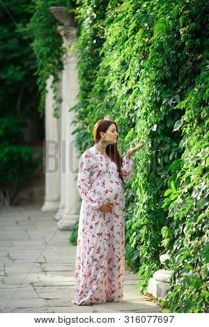 A Sweet Pregnant Woman Walks In The Park, Takes A Flower With Her Hand