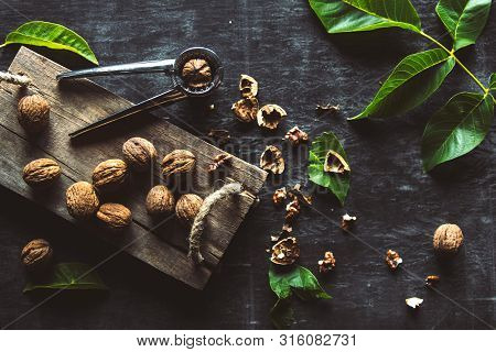 Walnuts On Dark Vintage Table. Healthy Food. Nuts Are Scattered On A Cutting Board. Old Vintage Tabl