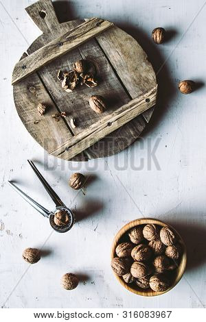 Walnuts In Wooden Bowl On Table With Nutcracker. A