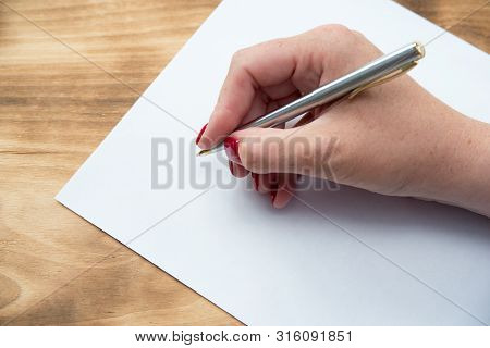 Womans Hand With Pen In Position To Write On Blank White Paper With Room To Add Text